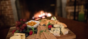 Cheese plate with crackers and olives on a wooden plank.