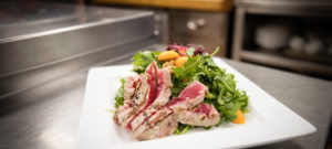 Seared tuna on a white plate with a dressed salad.