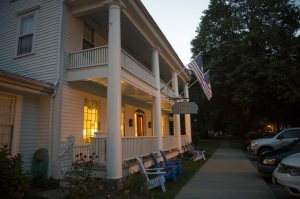 Large white home with two story porch and white columns lit up at night