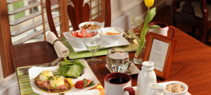Table set for breakfast with egg dish and fruits with coffee.