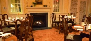 Dining room with wooden floors and a large fireplace.