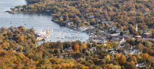 Aerial view of harbor surrounded by town nestled in fall foliage.