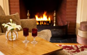 Two red wine glasses in foreground and a flickering fire in background