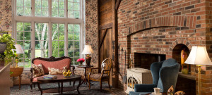Sitting room with expansive window and huge brick fireplace.