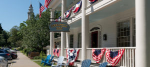 White house with two-story porch decorated with red white and blue bunting.