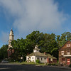 Historic New England town with brick church and white steeple surrounded by large trees.