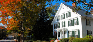 Large white house with black shutters surrounded by fall foliage on a sunny day.