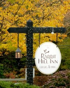 Rabbit Hill Inn's sign ith yellow tree in backgound.