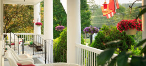 Large white columned front porch with chairs for resting and hanging flower baskets.