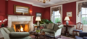 Parlor room with maroon walls and high ceilings with a fireplace and elegant seating area.