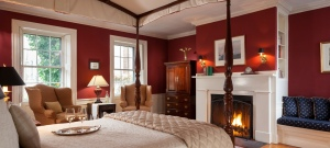 Bedroom with large wood four-poster bed, red walls and a fireplace.