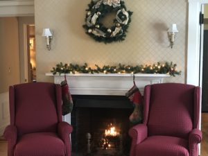 Fireplace with two chairs in front of it and decorated mantle at Captain's House Inn