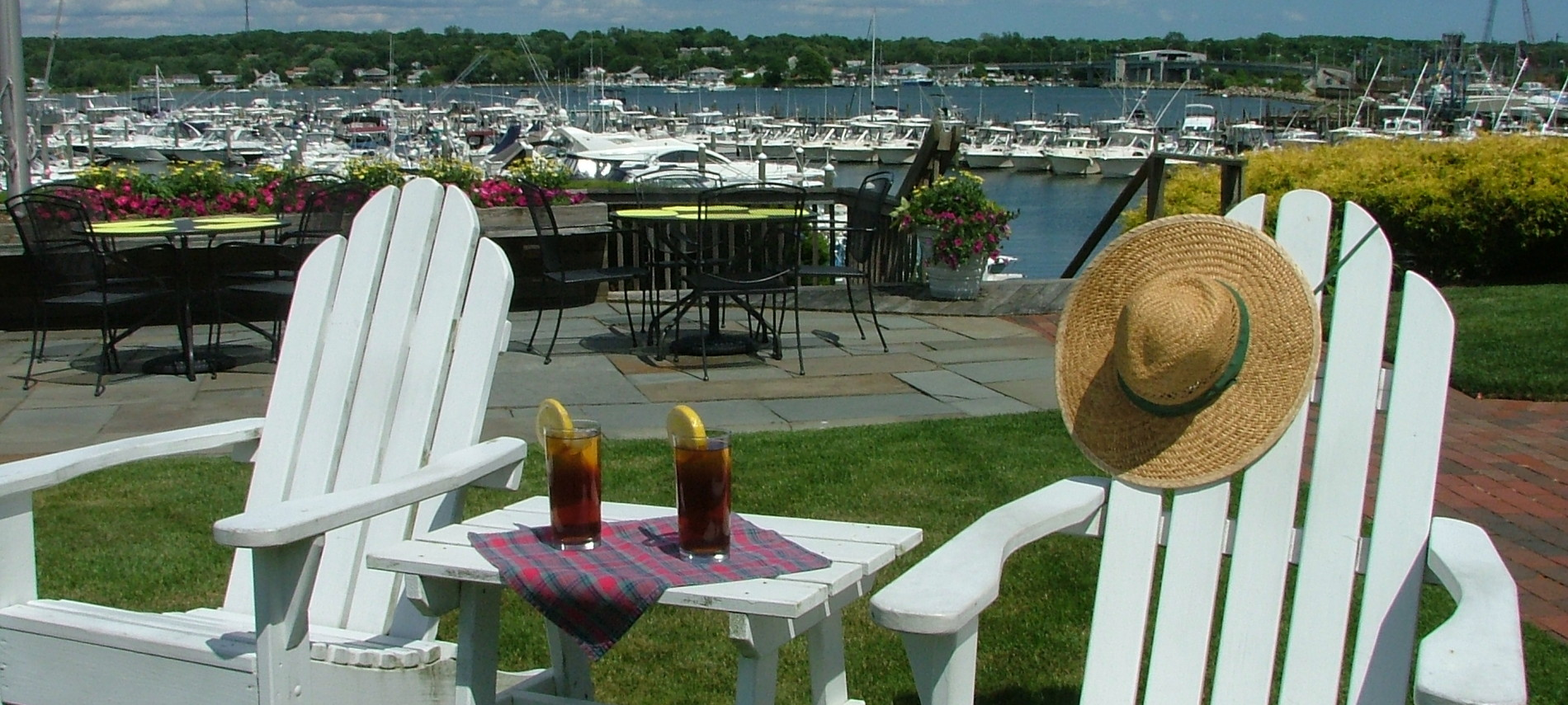 Two white adirondack chairs with a small table between overlook harbor view.