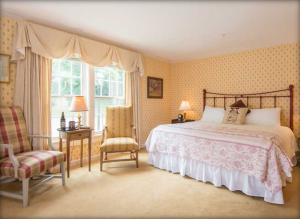 King sized brass bed in a cheerful well-lit bedroom.