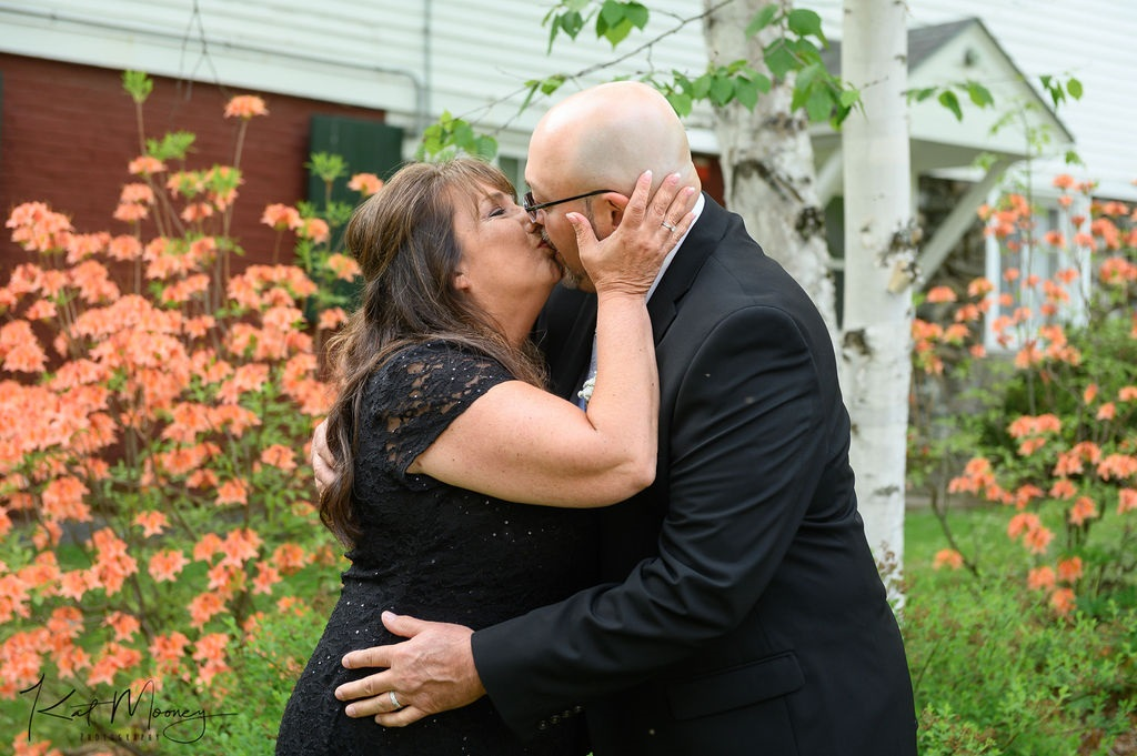 Rabbit Hill Inn guests kiss in front of the orange blooming bushes