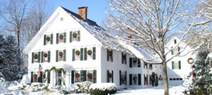 Large white house with black shutters on a winter day in the snow with bare trees.