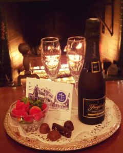 Guest room with fireplace,champagne and chocolates at Captain Jefferds Inn