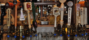 Several beer tap handles at a tavern with glassware on the bar.