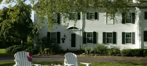 Large white house with back shutters with adirondack chairs in the forefront.