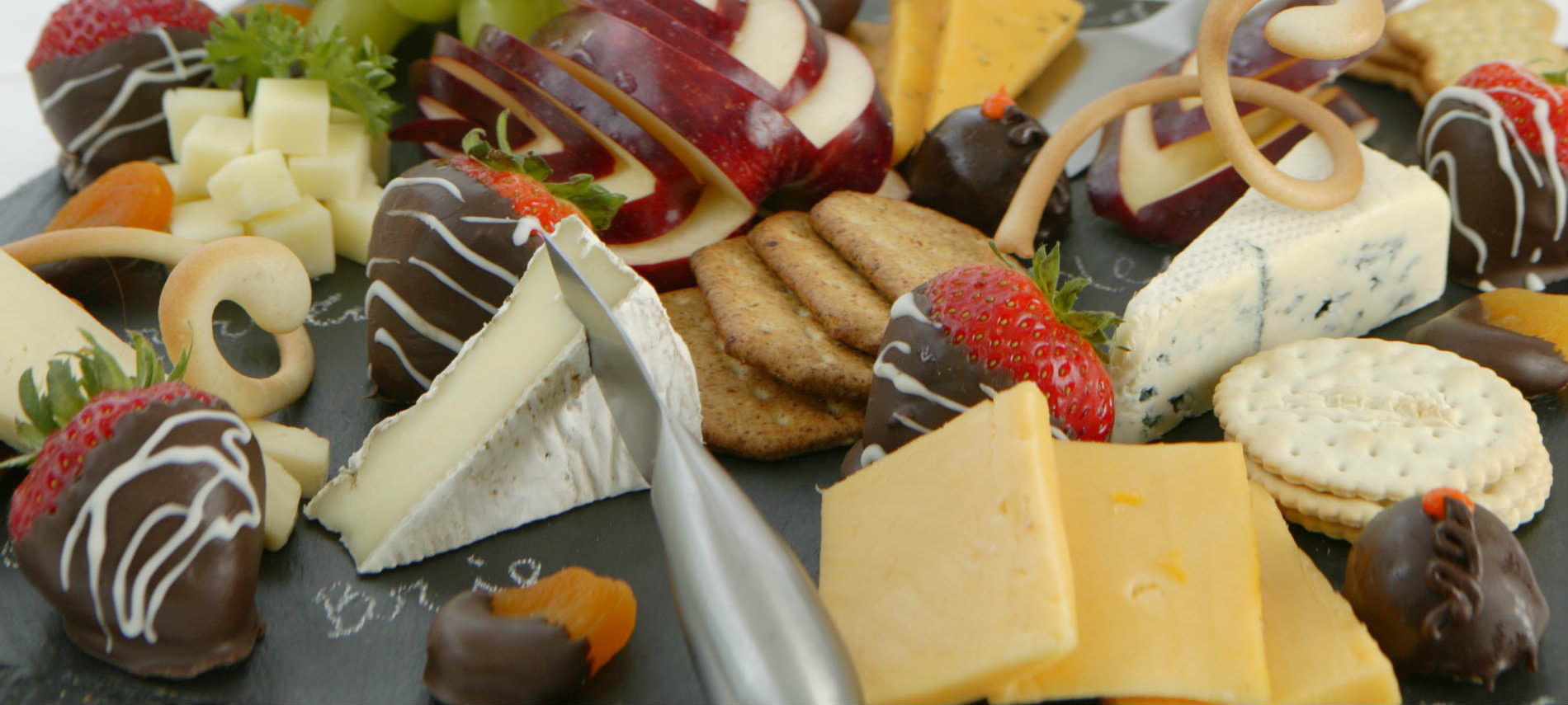 Lovely spread of various cheeses and crackers with chocolate-dipped strawberries.