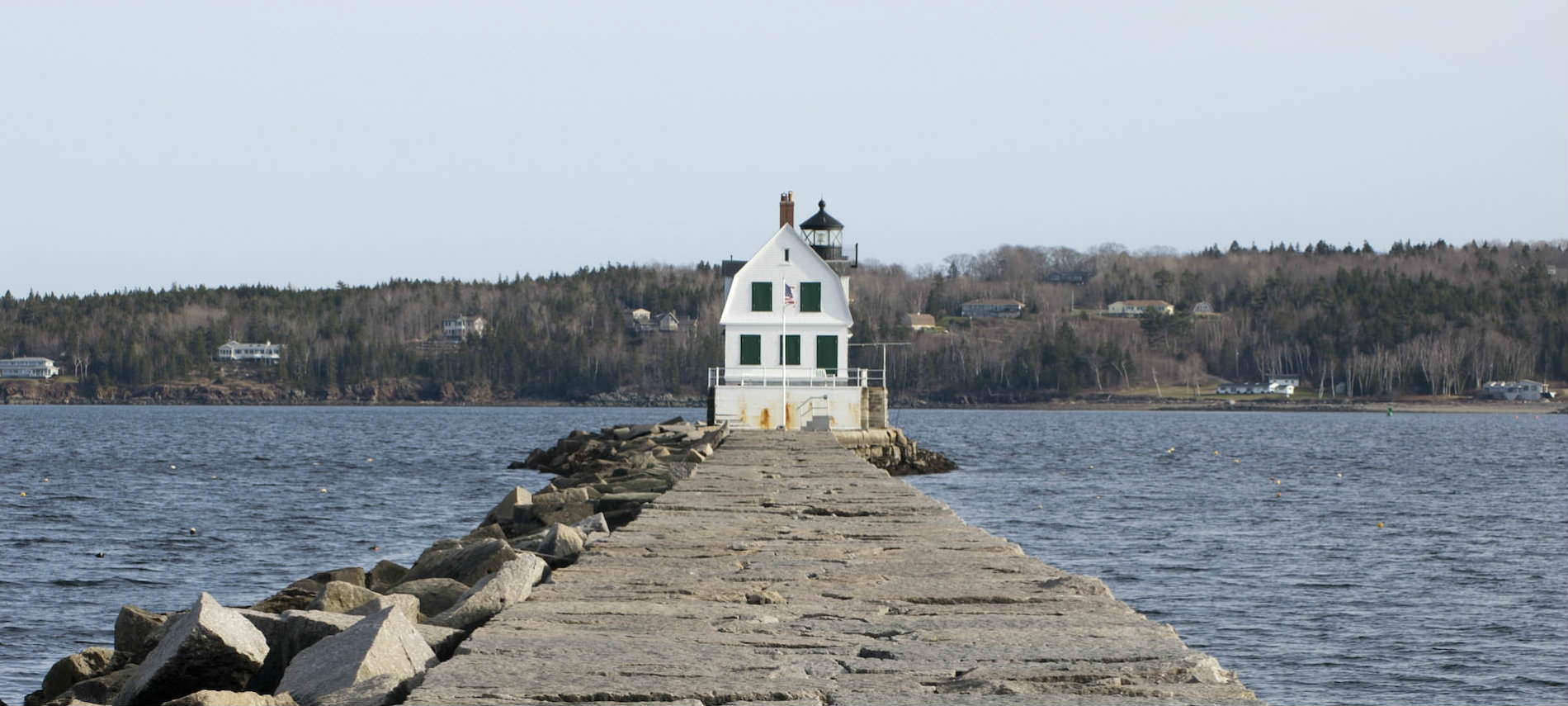 Stone pier leads to small white house surrounded by water and forested shoreline.