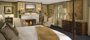 Suite with a large bed, striped wallpaper and a cheery fireplace.