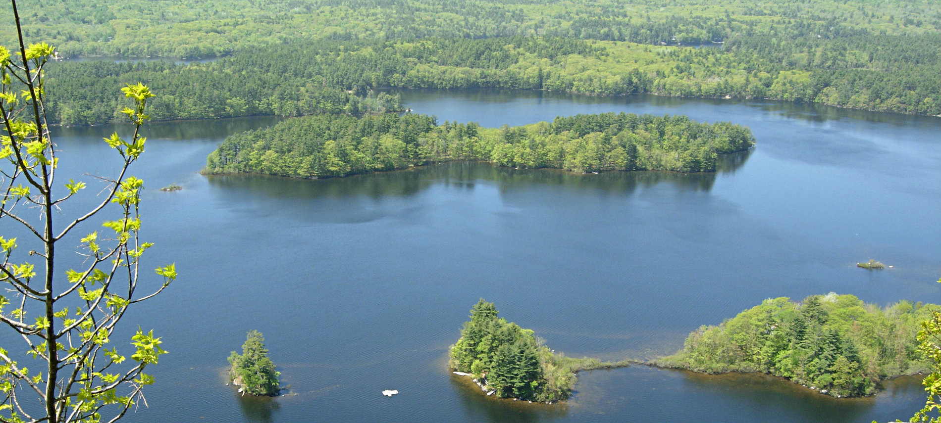 Overhead view of the water with several forested areas on a hazy summer day.