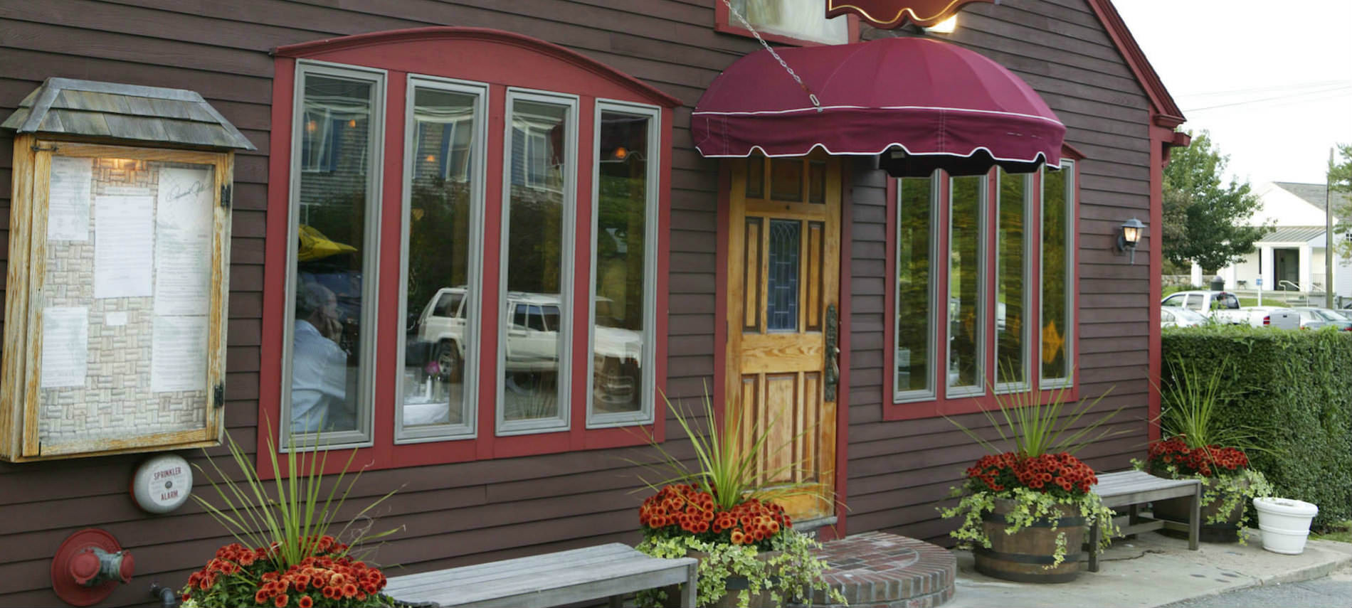 Building with brown siding and red trim, with colorful barrels of flowers around benches and porch..