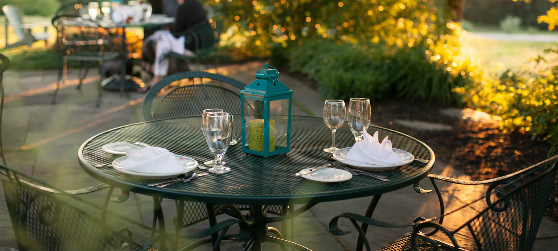 A green cafe table is set for two with white dishes on a brick patio.