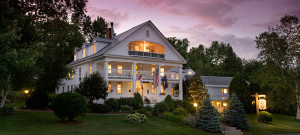 Beautiful large white manor house set on a hill surrounded by green lawn in the purple glow of sunset.