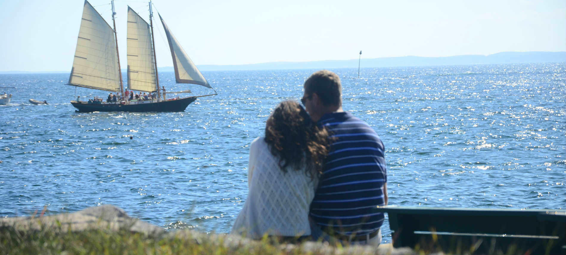 A couple sit close together on shore overlooking the sea and a white 3-sail boat.