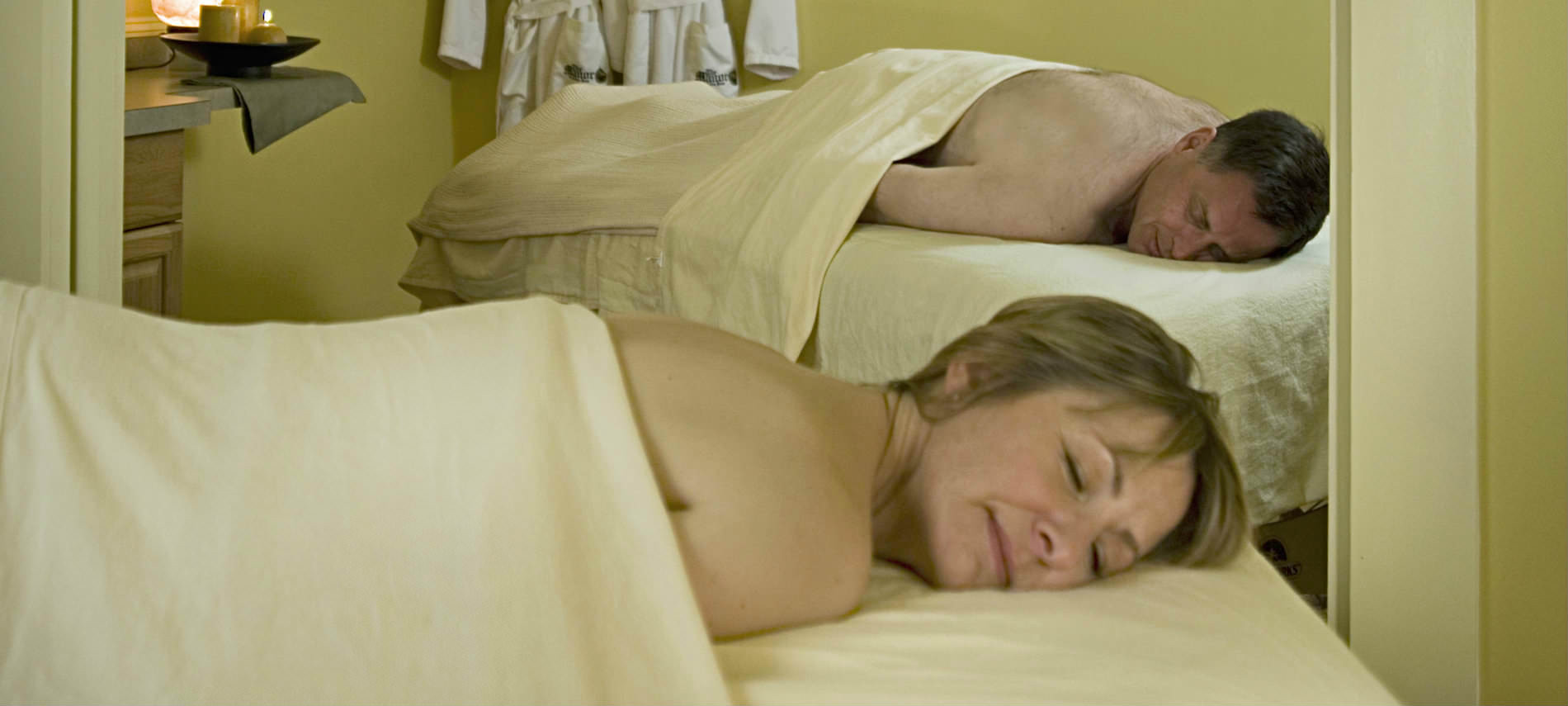 A mana nd woman covered with sheets relax on massage tables prior to a couples massage.