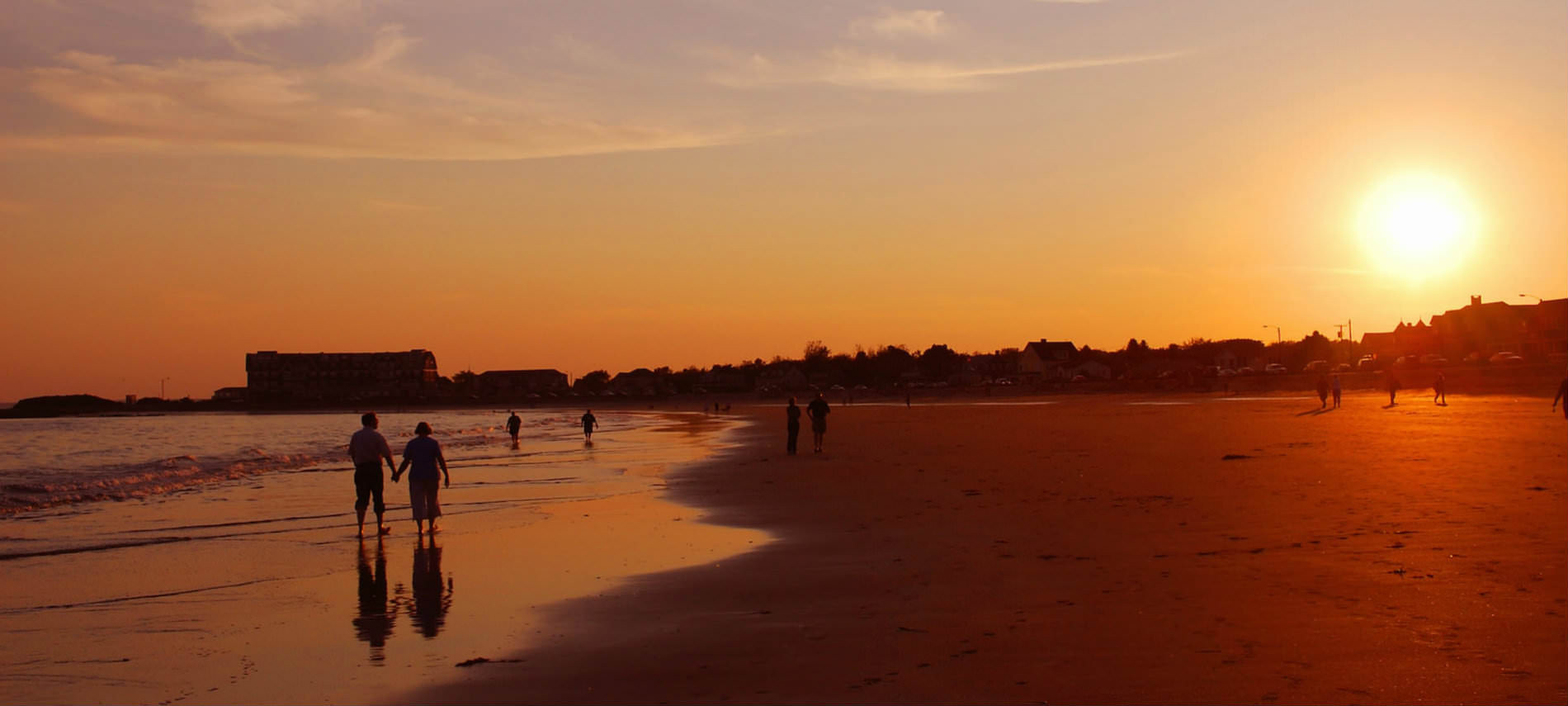 People walk along the shore, on the sand and in the shoreline, as the sun sets in a red blaze.