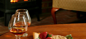 Cookies on a plate and two glasses of brandy site on a table next to a fireplace.