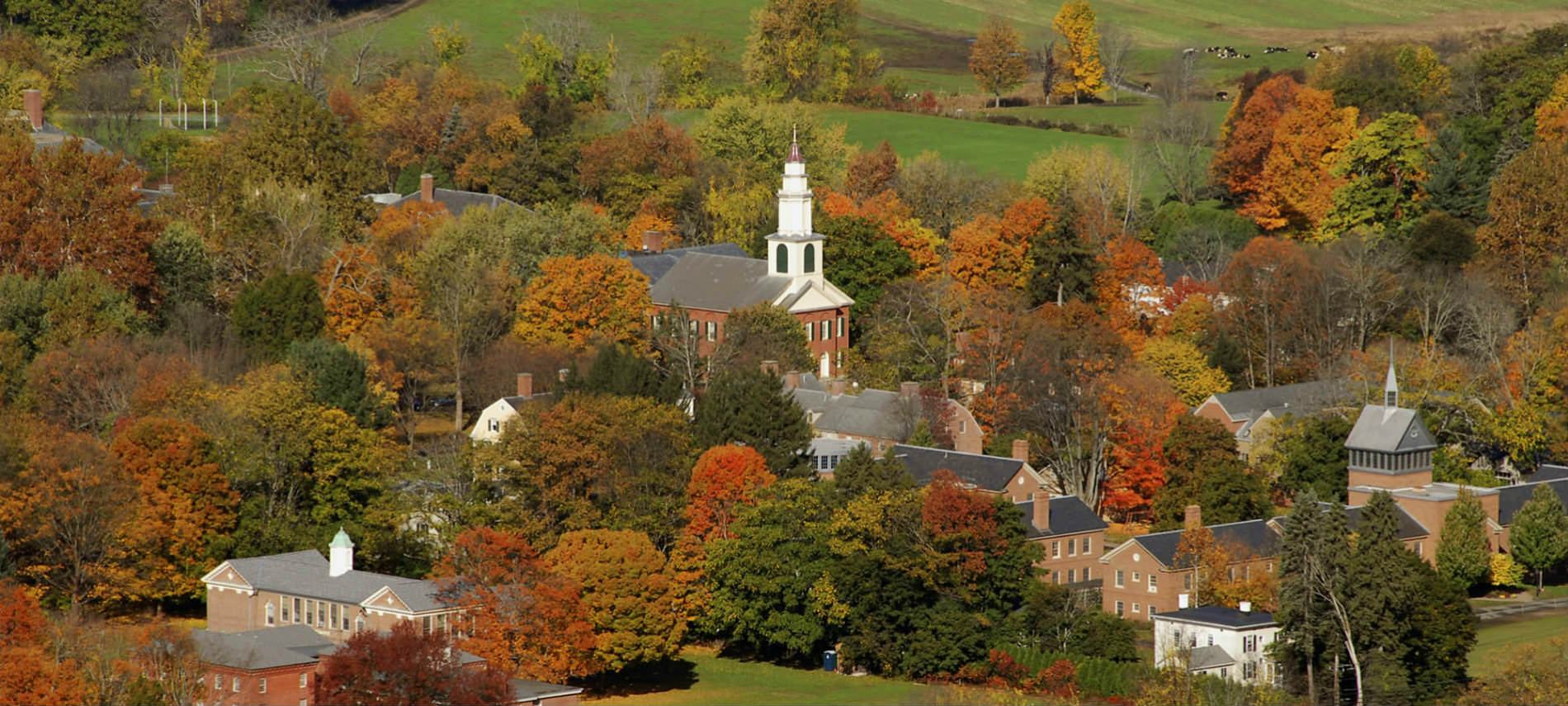 Historical white church with a tall steeple surrounded by homes and luxuriant fall foliage.