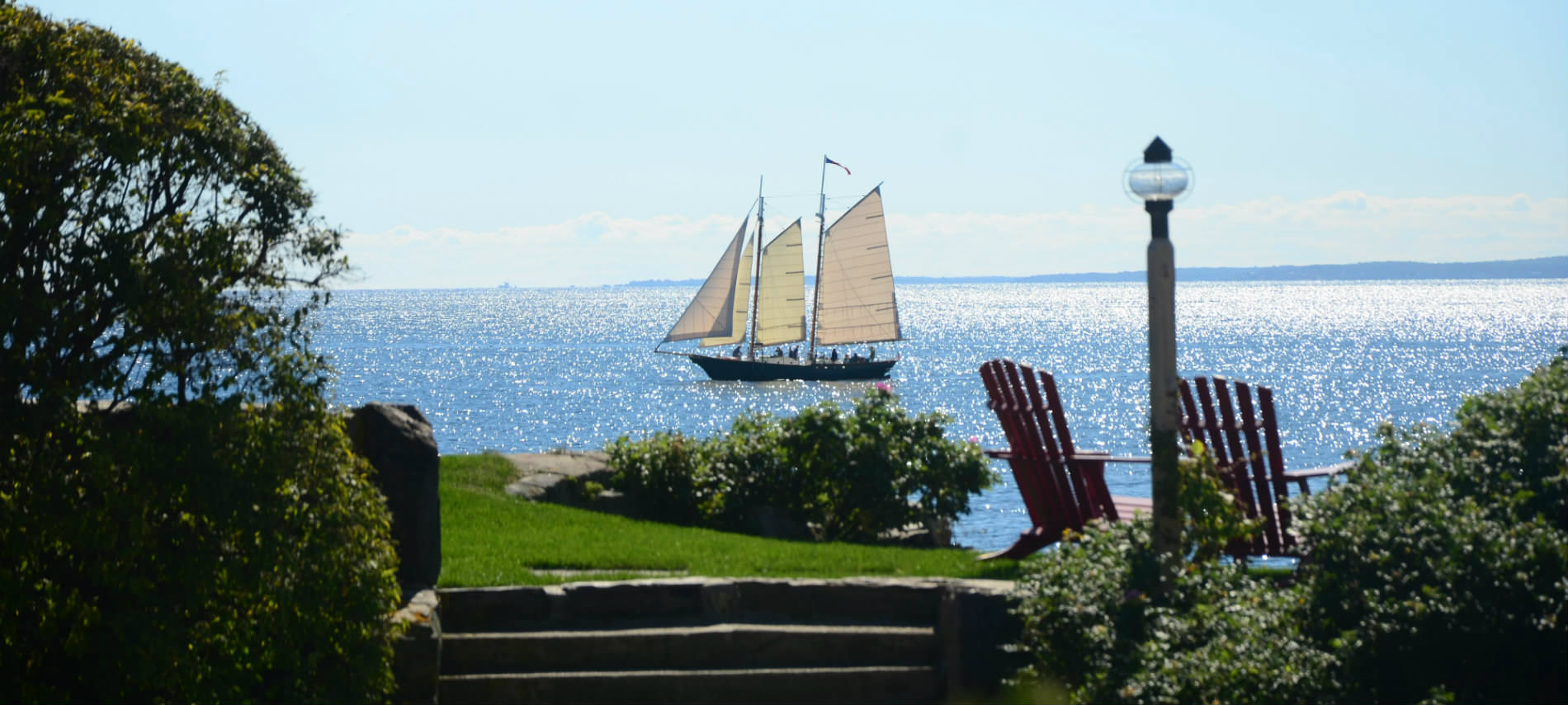Boat with three white sails floats past a lovely garden with two adirondack chairs overlooking the sea.