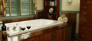 Whirlpool tub in wooden inset in well-appointed room.