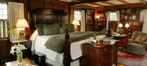 Elegant wooden paneled guest room with large four-post bed