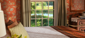 Guest room with bed made up in white and a large window overlooking water.