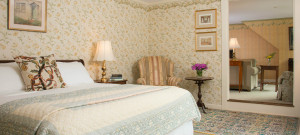 Large bedroom with pattered wallpaper and bed made up in soft coverings.