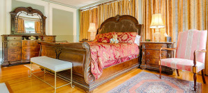 Beautiful antique sleigh bed covered in a rich red comforter in a bedroom with wooden floors.