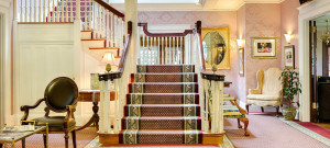 Graceful wooden painted staircase rises up to a landing then to second story of home.