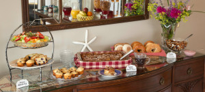 Breakfast buffet featuring cereal, breads and fresh fruit.
