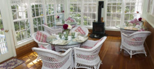 Bright and cheery breakfast room with wicker tables and chairs set for breakfast.