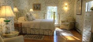 Cozy guestroom with brass bedstead and floral pattered wallpaper.