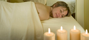 A woman covered with a sheet has a massage with candles burning.