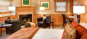 Bright bedroom with wood chair rail, fireplace and leather club chairs.