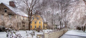 A New England street in winter with snow and picket fences.