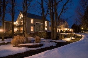 Large house lit up a night in the winter with large bare trees and snow all around.